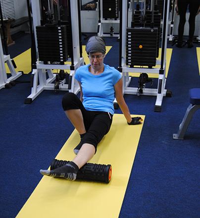 девушка делает купражнение с фитнес цилиндром